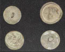 Metal buttons excavated at the site. The eagle button is bottom row left. The London button is bottom row right.