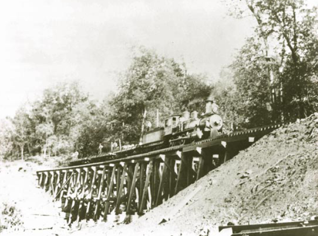 Locomotive Pee Wee leading a work train across one of the five mountain trestles of the Mineral Railroad, an eleven-mile line built and operated by Fort Payne & Eastern Railroad Company to convey materials from coal and fire clay deposits on Lookout Mountain to furnaces, ovens, and factories in Little Wills Valley.