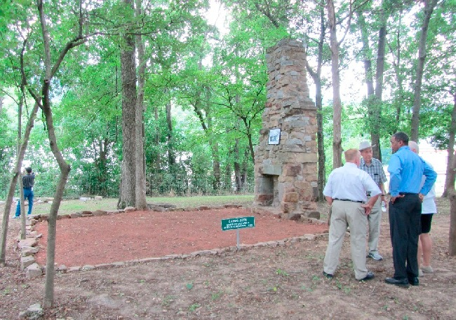 Attendees gather next to the Cabin's chimney.