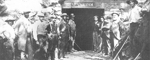 Local citizens at entrance to Manitou Cave in Fort Payne about 1878. Those identified are Harry Reed Godfrey and Orlando Godfrey, second and third on right, and Captain Williaim H. H. Minot, on left of cave entrance in straw hat. In cave entrance, left, Archie Spaulding; right, Mort Spaulding.